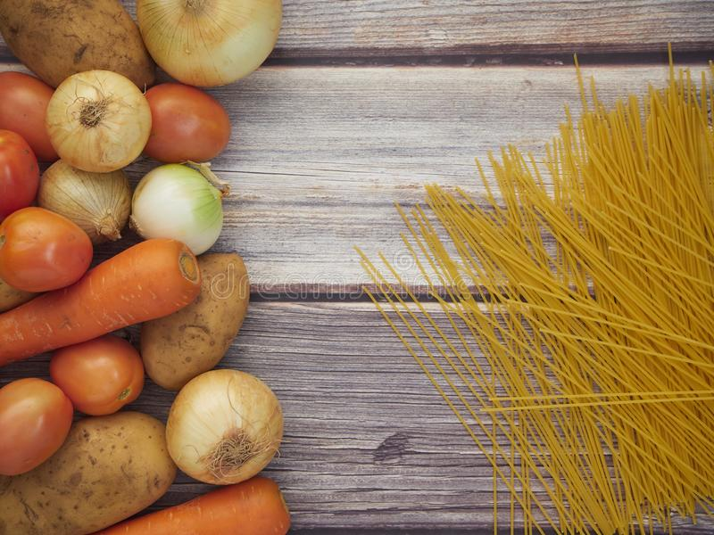 Fresh vegetables and spaghetti lines on old wooden tables royalty free stock image