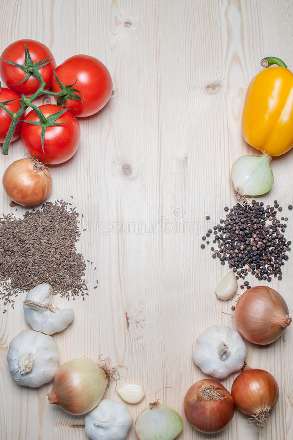 Fresh vegetables and spices on cutting board. Fresh tomato, pepper, onion, garlic and spices on cutting board stock image