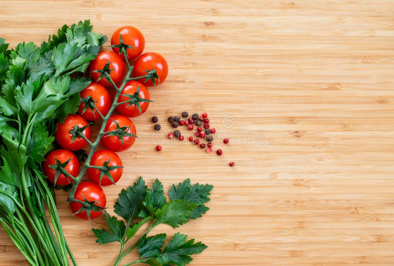 Fresh vegetables on the table, copy space. Food background. Flat lay. Cherry tomatoes, a bunch of parsley, black and red peppers royalty free stock photography