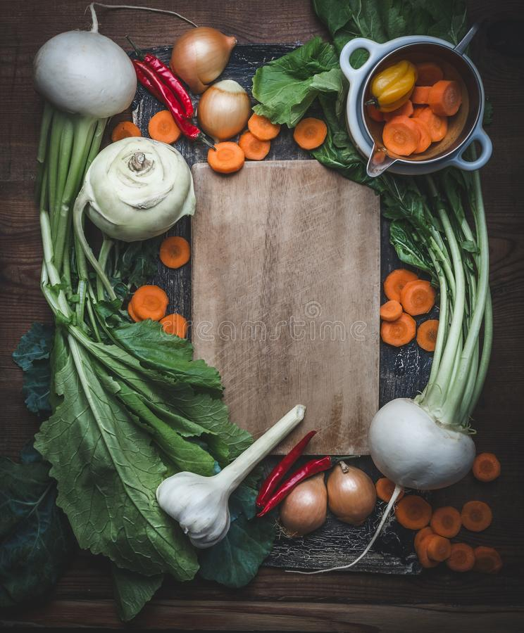 Fresh vegetables for tasty vegetarian cooking around wooden cutting board. Top view. Copy space. Frame. Fresh vegetables for tasty vegetarian cooking around stock images