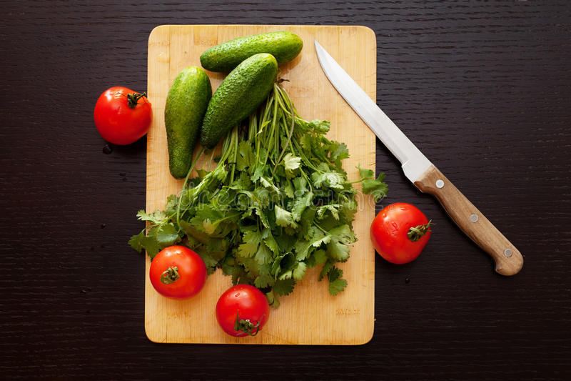 Fresh vegetables. Fresh tomatoes and cucumbers with cilantro on the wooden background royalty free stock photo