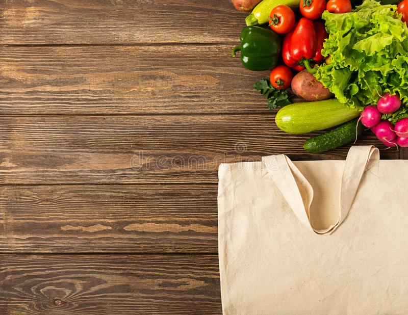 Fresh vegetables tomatoes zucchini greens eco bag made of natural cotton wooden background. Healthy proper nutrition. stock photos