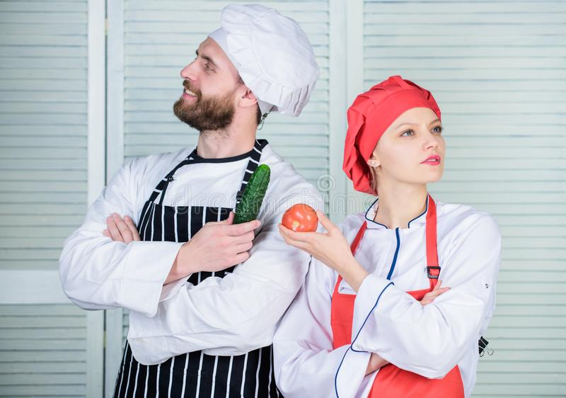Fresh vegetables. Vegetarian family. Woman and bearded man cooking together. Chefs of organic food restaurant. Cooking royalty free stock photos