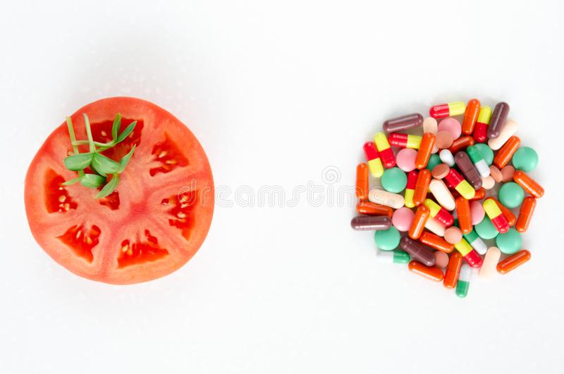 Fresh vegetables versus pills. A slice of tomato and fresh sprouts of sunflower against a heap of multi-colored pills stock photos