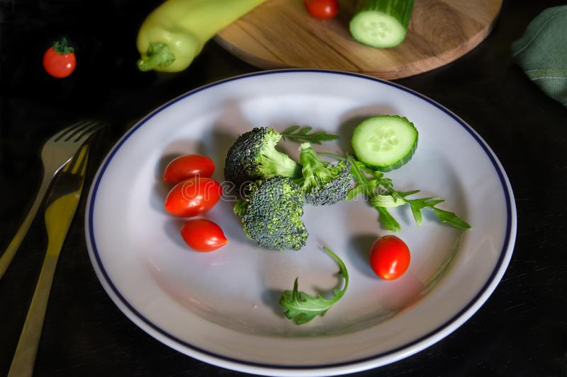 Fresh vegetables on white plate. Broccoli sliced cucumbers and cherry/grape tomatoes. stock photo