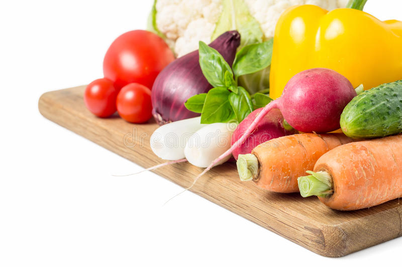 Fresh vegetables at wood cutting board on white stock images