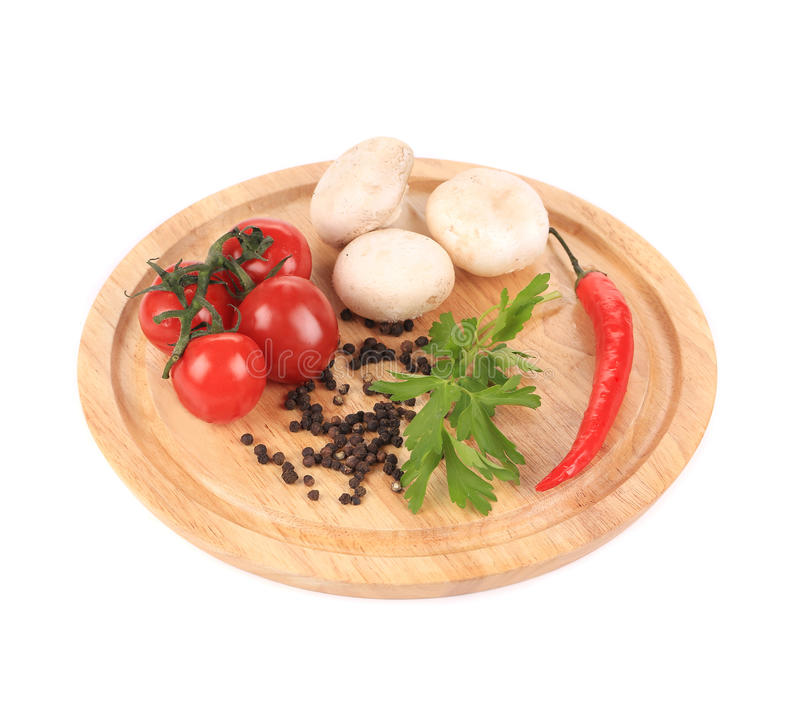Fresh vegetables on wooden platter. Isolated on a white background royalty free stock photos