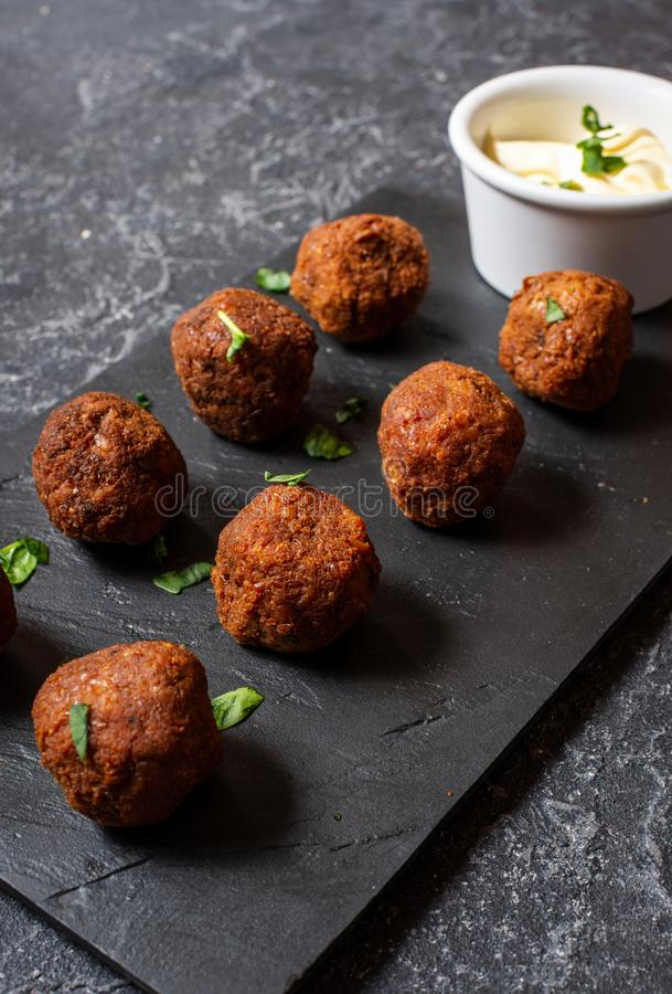 Fresh vegetarian falafel balls with sauce on stone background stock images