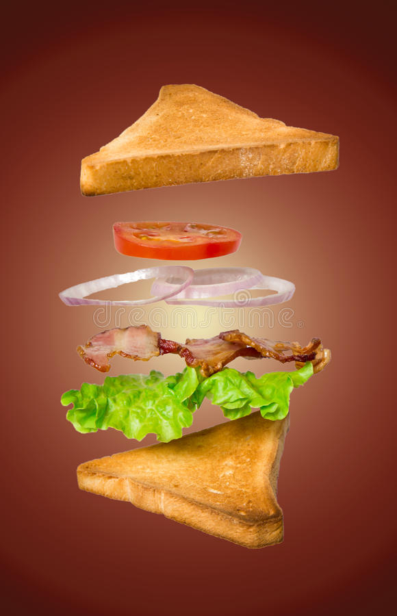 Fresh vegetarian sandwich with flying ingredients isolated on dark background royalty free stock photos