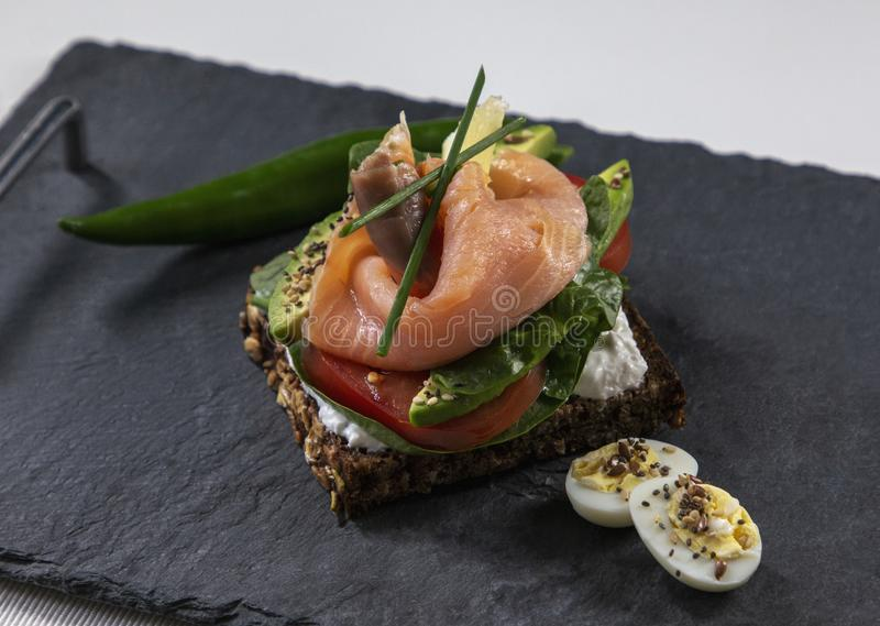 Fresh  vegetarian sandwich with red fish and avocado. stock photo