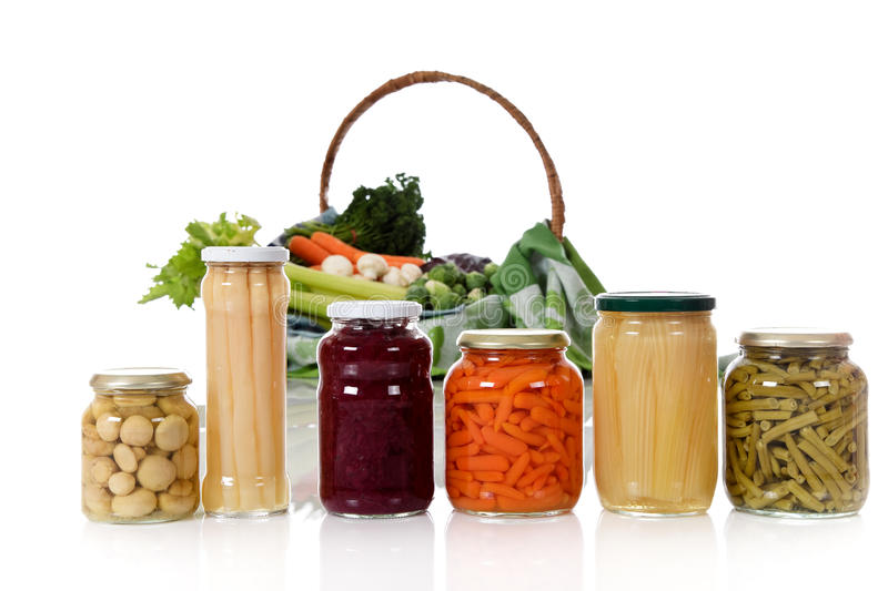 Fresh versus canned vegetables. Canned vegetables in jars versus fresh vegetables in basket. Focus on jars. Healthy eating concept. Studio shot. White background stock images