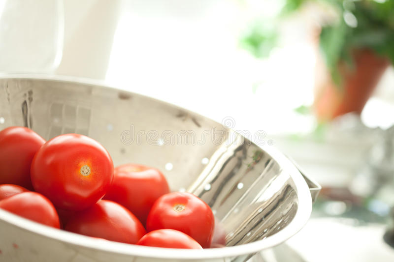 Fresh, Vibrant Roma Tomatoes in Colander with Wate stock photo