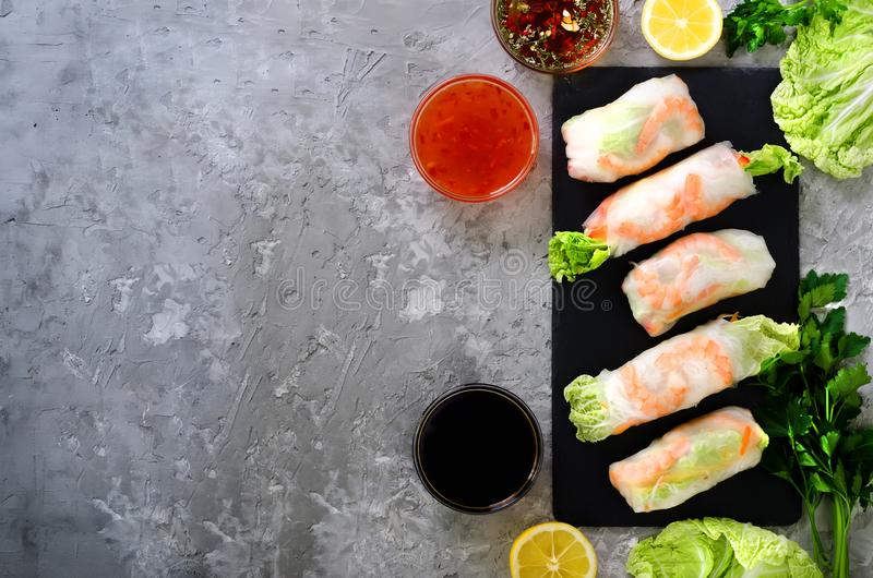 Fresh Vietnamese, Asian, Chinese food frame on grey concrete background. Spring rolls rice paper, lettuce, salad. Vermicelli, noodles, shrimps, fish sauce stock photo