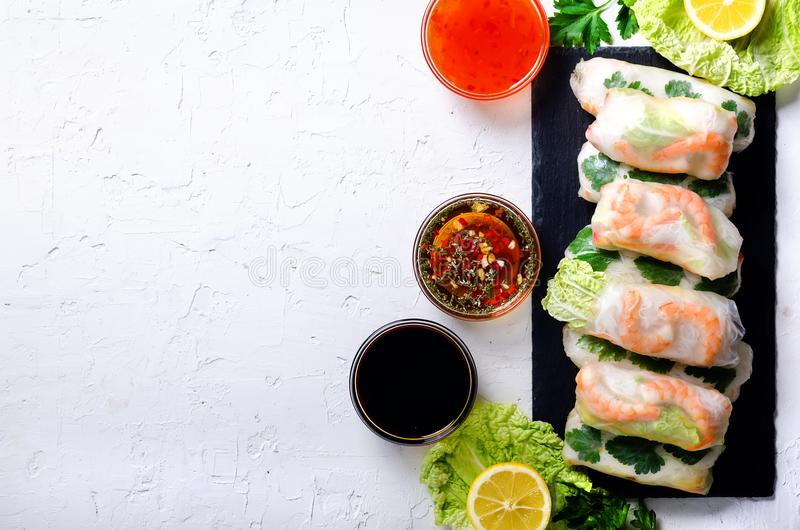 Fresh Vietnamese, Asian, Chinese food frame on white concrete background. Spring rolls rice paper, lettuce, salad. Vermicelli, noodles, shrimps, fish sauce stock images