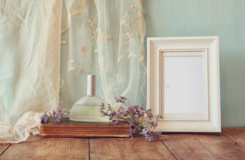 Fresh vintage perfume bottle next to aromatic flowers and antique blank frame on wooden table. retro filtered image stock photo