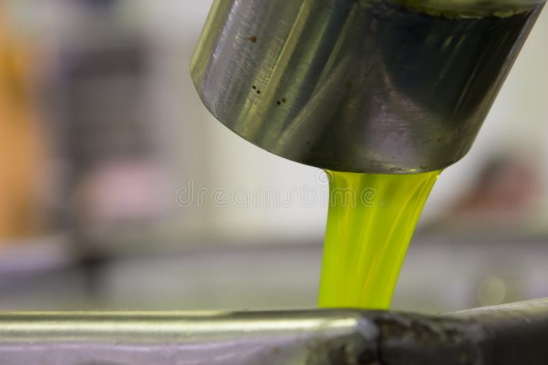Fresh virgin olive oil pouring into tank at a cold-press factory after the olive harvesting, Crete, Greece. stock images