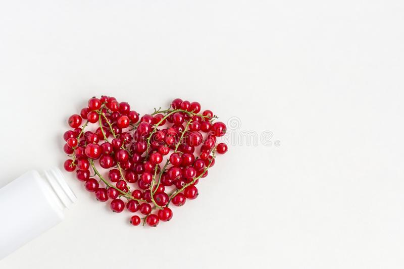Fresh vitamins berries as shape of heart  from medicine white pill bottle on white background royalty free stock image