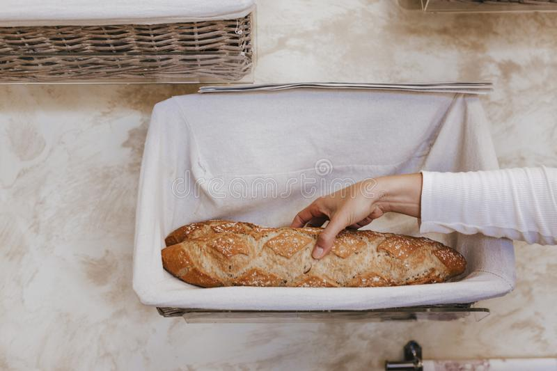 Fresh and warm. close up woman hand holding fresh and warm bread just from the oven. Bakery concept stock photos
