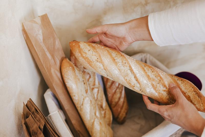 Fresh and warm. close up woman hand holding fresh and warm bread just from the oven. Bakery concept stock photo