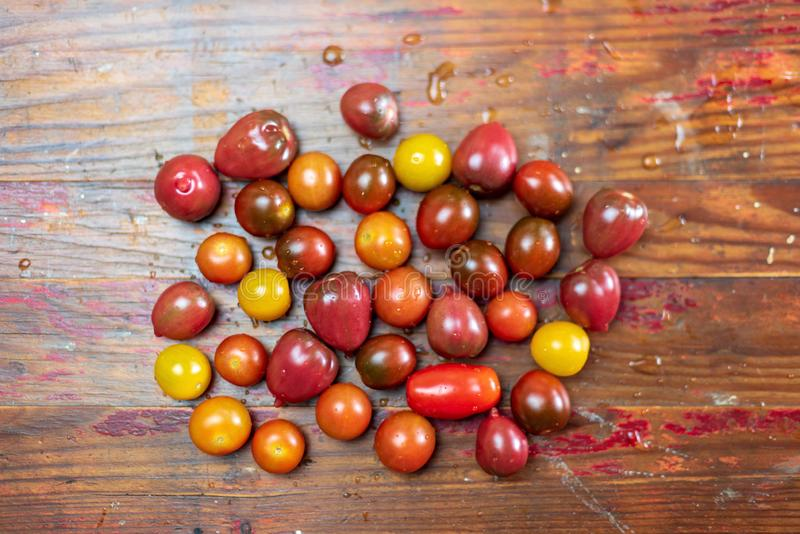 Fresh washed heirloom cherry tomatoes on wood background royalty free stock photography