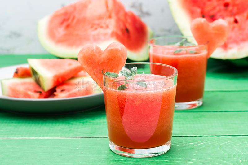 Fresh watermelon blended drink with mint leaves and a heart of watermelon in glasses. On a wooden table stock photos
