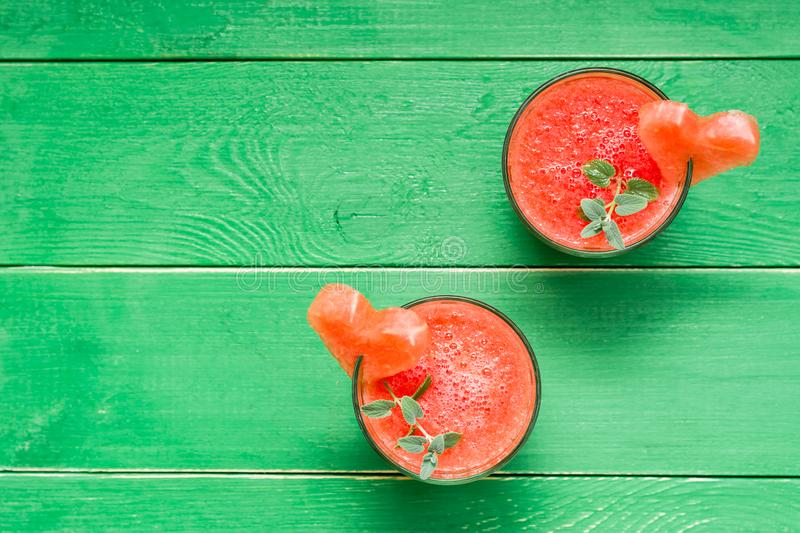 Fresh watermelon blended drink with mint leaves and a heart of watermelon in glasses on a wooden table. Top view royalty free stock photography