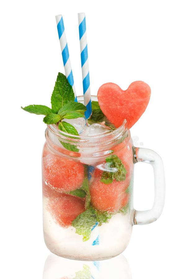 Fresh watermelon drink in Mason jar with mint, straws and heart shaped watermelon slice isolated on white background. Watermelon drink in Mason jar with mint stock photo