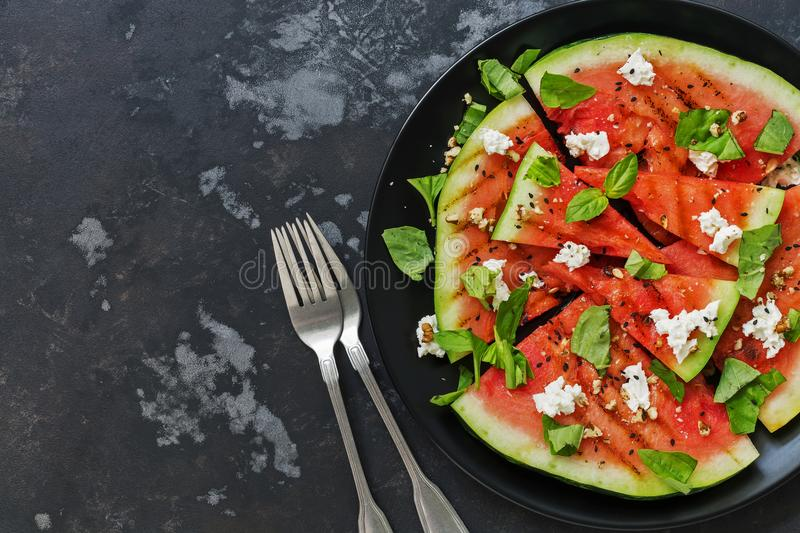 A fresh watermelon grill with feta cheese and greens on a rustic dark gray background. View from above, flat lay. royalty free stock photography