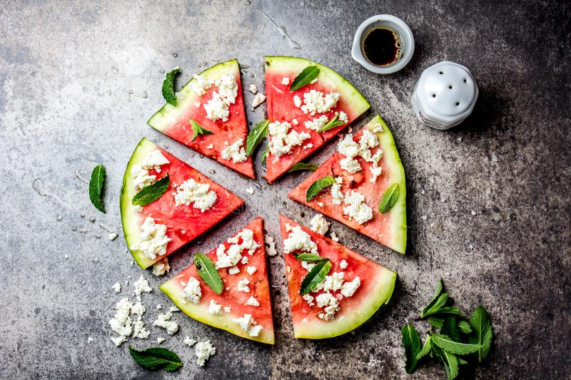 Fresh watermelon pizza salad with feta cheese, mint, salt and oil on stone background royalty free stock images