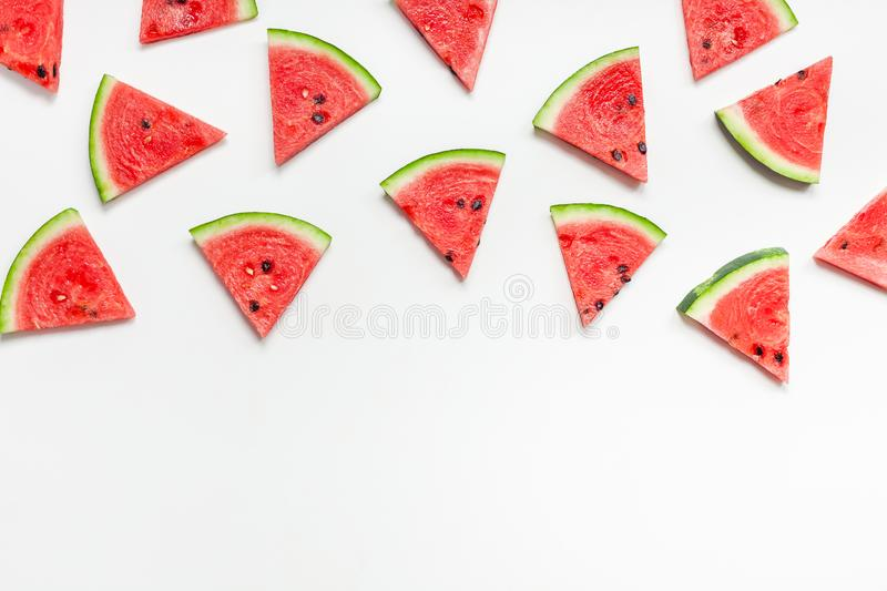 Fresh watermelon slices pattern. Creative scandinavian style flat lay top view of fresh watermelon slices on white table background copy space. Minimal summer stock image