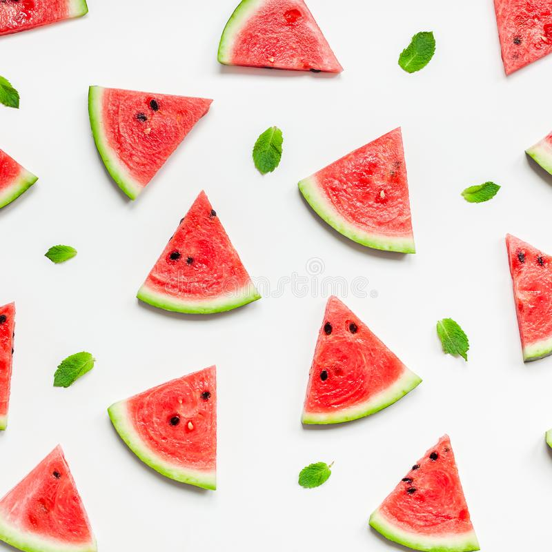 Fresh watermelon slices pattern. Creative scandinavian style flat lay top view of fresh watermelon slices on white table background copy space. Minimal summer royalty free stock photography