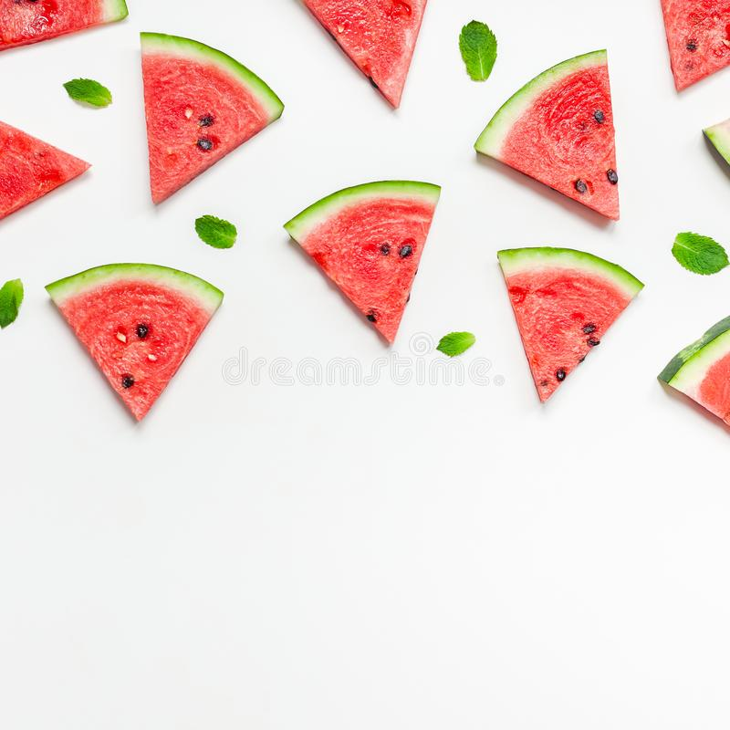 Fresh watermelon slices pattern. Creative scandinavian style flat lay top view of fresh watermelon slices on white table background copy space. Minimal summer stock photos