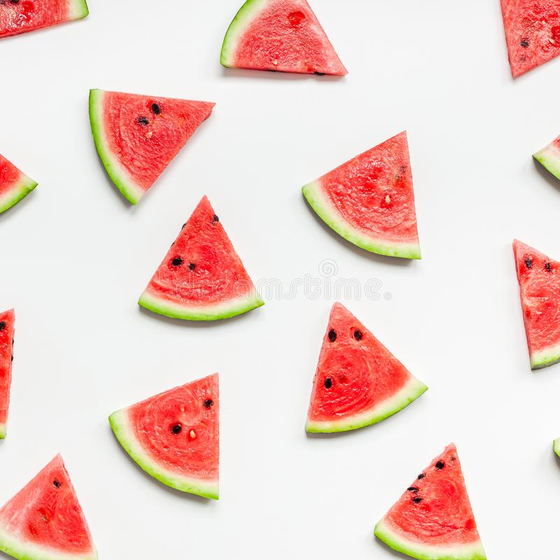 Fresh watermelon slices pattern. Creative scandinavian style flat lay top view of fresh watermelon slices on white table background copy space. Minimal summer stock photography