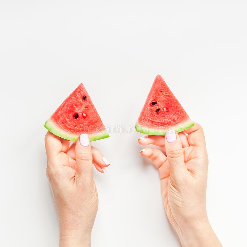 Fresh watermelon slices in woman hands. Creative scandinavian style flat lay top view of fresh watermelon slices in woman hands on white table background copy stock photography