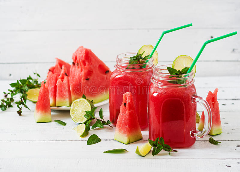 Fresh watermelon smoothies with lime and mint. On white wooden background royalty free stock image