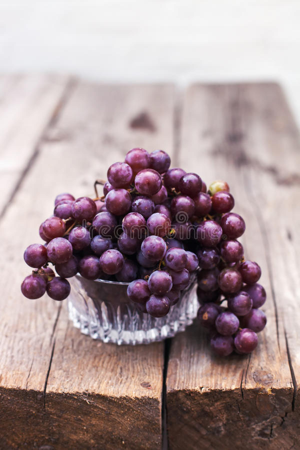 Fresh wet dark blue grapes with leaves and vines on an old wooden table in rustic style royalty free stock photography