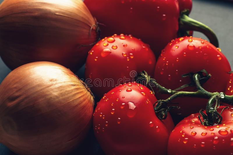 Fresh wet tomatoes in drops of water, golden onion, bell pepper royalty free stock photography