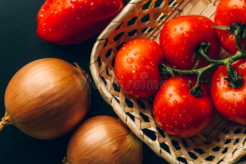 Fresh wet tomatoes in drops of water, golden onion, bell pepper, top view royalty free stock photos