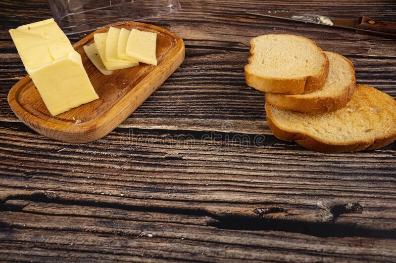Fresh wheat bread toast and a wooden butter dish with a piece of butter and slices of cheese on a wooden background. Close up.  royalty free stock images