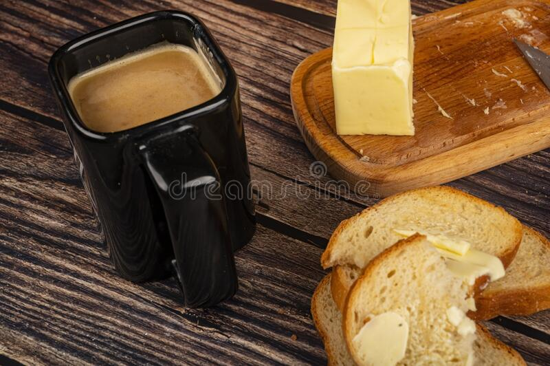 Fresh wheat toast with butter, a wooden butter dish with a piece of butter and a mug of coffee with milk on a wooden background. Close up royalty free stock photos