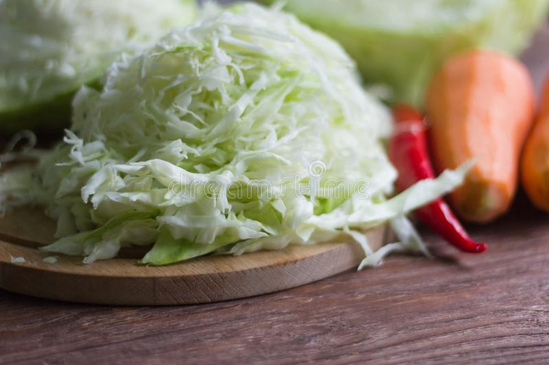 Fresh white cabbage shredded for pickling, carrots and chili on a wooden table stock photo