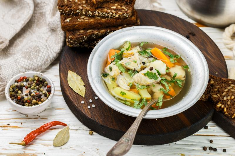 Fresh white fish soup with carrots, potatoes, onions, herbs and spices stock photos