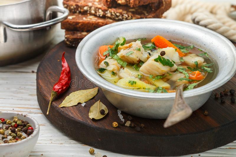 Fresh white fish soup with carrots, potatoes, onions, herbs and spices royalty free stock images
