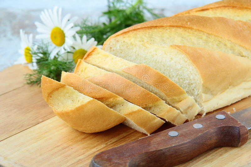 Fresh white loaf of bread with a knife royalty free stock images