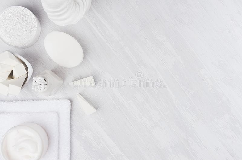 Fresh white natural cosmetics - white cream, soap, salt, towel and bath accessories on soft light white wood table, border. Fresh white natural cosmetics stock image