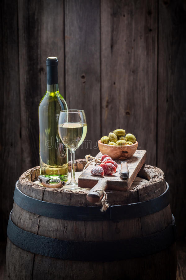 Fresh white wine with olives and cold cuts stock photo