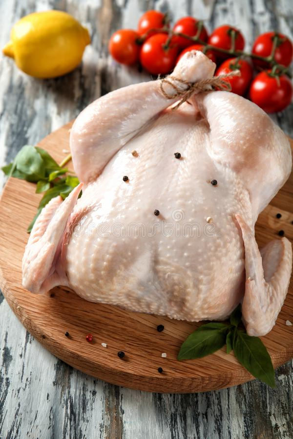 Fresh whole chicken with tomatoes and lemon. On wooden board stock photography