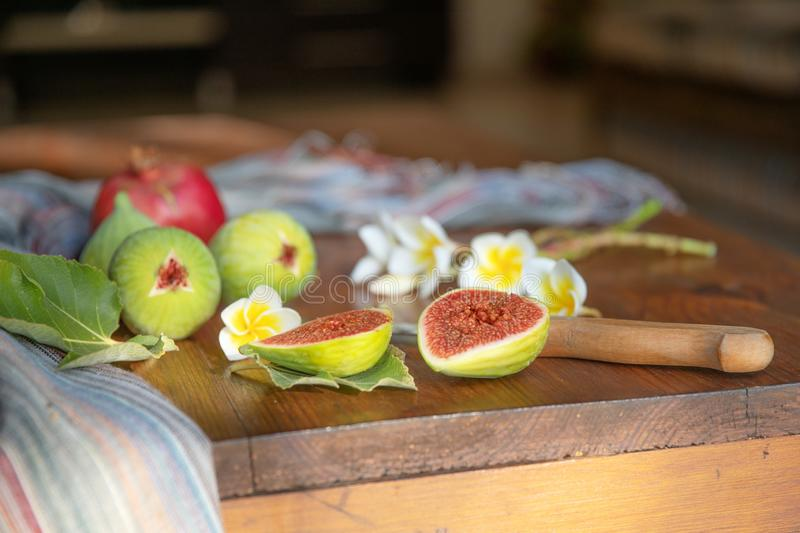Fresh whole and cut fruits figs, pomegranate and exotic plumeria flowers on wooden kitchen table background. Still life.  royalty free stock photo