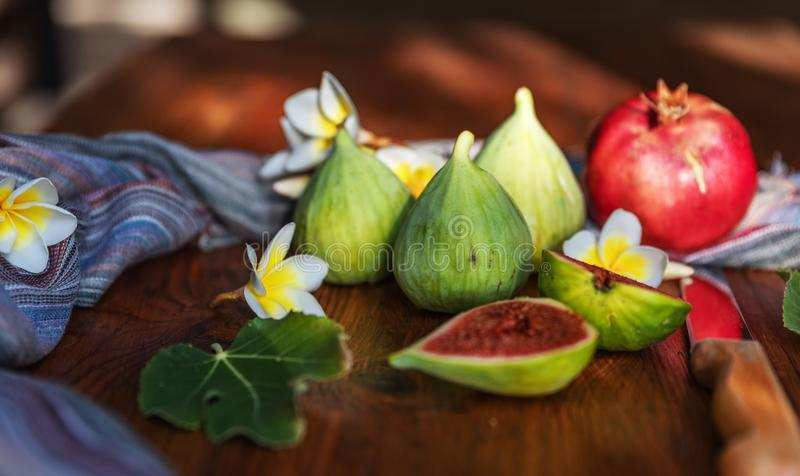 Fresh whole and cut fruits figs, pomegranate and exotic plumeria flowers on wooden table background. Still life stock image