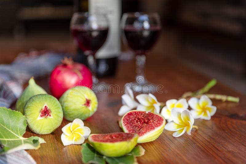 Fresh whole and cut fruits figs, pomegranate and exotic plumeria flowers on wooden table with bottle of wine and glasses. Background. Still life royalty free stock images